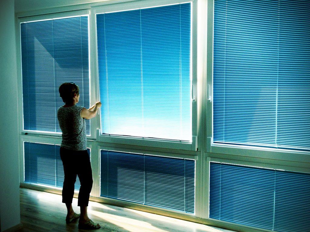 Woman with window blinds